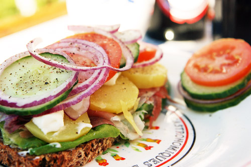 Et stykke med kartoffel, rødløg, agurk, tomat, mayonnaise og serrano skinke